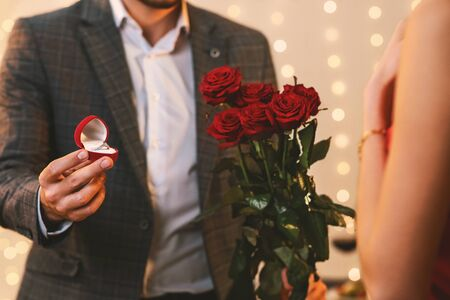 Valentines Day Proposal. Romantic Man With Engagement Ring And Roses Flowers Asking Girlfriend To Marry Him