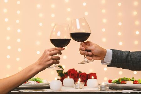 Toast for us. Romantic couple holding and clinking two glasses of red wine on date in restaurant, closeup, copy space