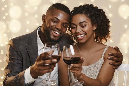 Portrait of happy african couple celebrating St. Valentines Day at restaurant, drinking red wine and embracing, close up