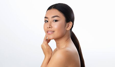 Asian beauty. Portrait of beautiful girl touching her soft skin and looking at camera over white background Imagens