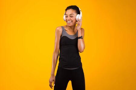Fitness Playlist. Joyful African American Woman In Earphones Listening To Music Posing Over Yellow Background. Studio Shot