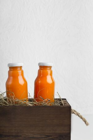 Natural organic and healthy orange juice in glass bottles in creative box on white background, vertical panorama, copy space Zdjęcie Seryjne