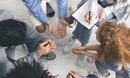 Trust circle. Diverse people sharing their problems with psychologist at group therapy session, counselor taking notes to clipboard, top view