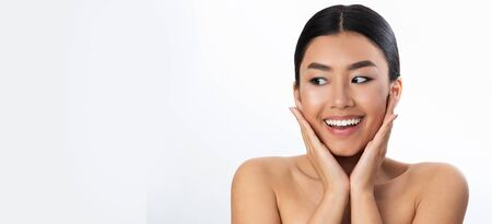 Surprised asian woman touching her cheeks and looking at free space on white background, panorama Imagens