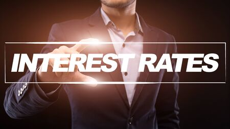 Profitable investment offer. Unrecognizable businessman holding framed interest rates inscription with fingers, posing over black background, panorama
