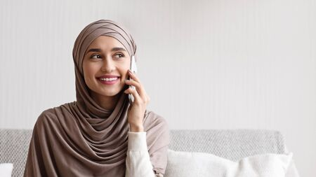 Unexpected call. Young arabic girl in headscarf having pleasant phone conversation at home, smiling and looking away, panorama with free space