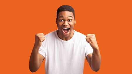 Big Luck. Excited black guy screaming with joy, making winner gesture isolated over orange wall, panorama, copyspace Stock fotó
