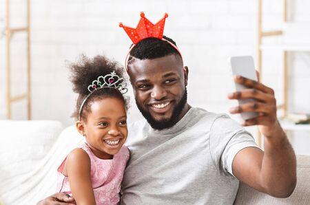 Alegre padre de familia afro e hija en edad preescolar divirtiéndose en casa, tomando selfie, con coronas