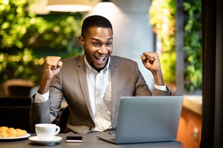 Great Success. Happy african american businessman looking at laptop screaming with joy, raising fists in cafe, copyspace