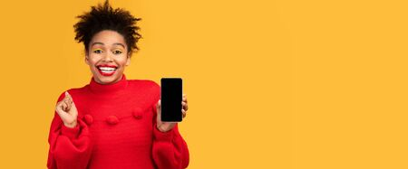 Celebrating Great News. Emotional afro girl shaking fist holding phone with blank screen, yellow wall, panorama. Mock up