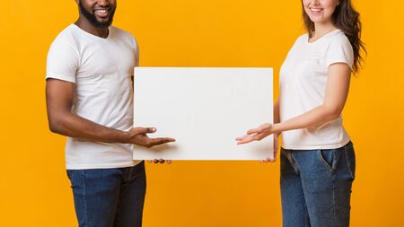 White blank placard for your advertisement in hands of interracial spouses, multiracial couple pointing at copy space with open palms, crop, panorama