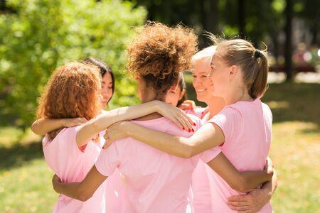 Cancer du sein. Femmes multiraciales en T-shirts à ruban rose étreignant debout en cercle pendant la réunion du groupe de soutien dans le parc. Mise au point sélective