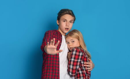 Domestic violence victims. Elder brother embracing his little sister, protecting her from parents abuse, blue background with free space