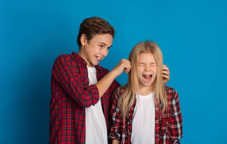 Concept de relation fraternelle. Frère aîné taquinant la petite soeur, tirant ses oreilles jusqu'à ce qu'elle crie, debout ensemble sur fond bleu studio