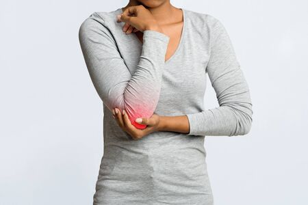 Cropped of young afro woman having acute pain in elbow joint, grey background