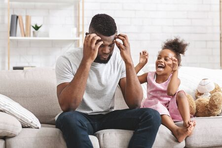 Tired african father holding head because of naughty spoiled little daughter, girl crying and shouting loudly. Family, relationships and problems concept