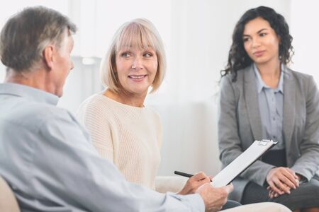 Senior Health Insurance Concept. Mature couple making agreement with sale agent, senior woman signing contract