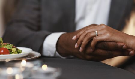 Cropped of black man holding woman hand with ring on, got engaged