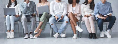 Przycięty obraz młodych wielorasowych ludzi z laptopami i książkami siedzącymi w kolejce, czekającymi na rozmowę kwalifikacyjną, panorama