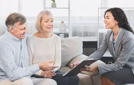 Firme aquí por favor. Agente de bienes raíces mexicano que ofrece propiedad de vivienda y seguro de vida a una pareja de ancianos