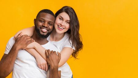 Interracial couple in love. Portrait of happy multiracial sweethearts embracing and posing together over yellow background, panorama with copy space