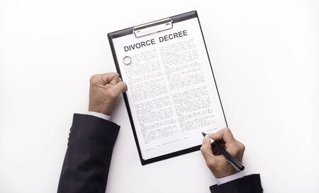 Husband Filing divorce papers or premarital agreement prepared by lawyer. Wedding ring, panorama, white background