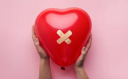 First Aid Band Plaster Strip Medical Patch glued on red heart balloon in woman hands on pink background. Heart broken, Love and Valentines day concept.