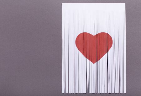 Broken heart, loss, ended relationship concept. Sign of heart drawn a piece of paper, gray background, copy space