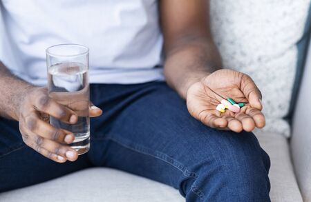 Virus protection. Pile of pills with water glass in hands of african man, close up