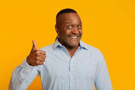 Happy middle aged african man gesturing thumb up, orange studio background