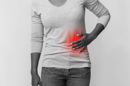 Black and white cropped photo of african woman rubbing her left side, pancreatitis concept