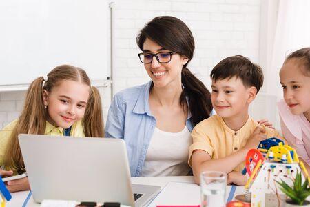 Stam les. Leerlingen en leraar kijken naar robotica-video op laptop, studeren aan naschoolse les Stockfoto