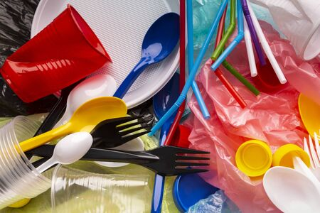 Borraccia usa e getta, cannucce e borsa per la spesa, articolo in plastica monouso. Inquinamento da plastica che colpisce l'ecologia marina. Concetto di ambiente. Vista dall'alto. Archivio Fotografico