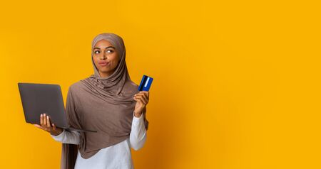 Online Reservations Concept. Thoughtful Black Islamic Girl In Headscarf Holding Laptop And Credit Card, Planning Vacation, Yellow Background, Panorama