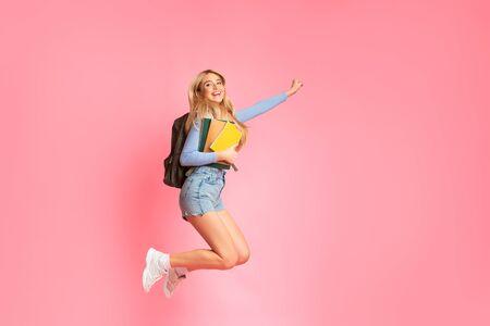 Sí, lo he hecho. Chica estudiante feliz con mochila saltando en el estudio, sosteniendo cuadernos. Espacio libre, longitud completa Foto de archivo