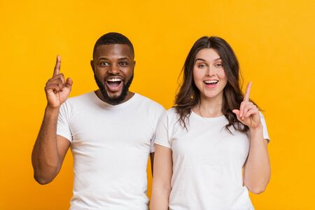 Couple Offer. Cheerful Afro Guy And Young Woman Having Idea, Foung Problem Solution, Pointing Fingers Up Over Yellow Background, Free Space