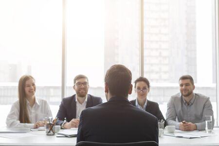 Solicitante masculino hablando en la entrevista de trabajo a la comisión de recursos humanos, vista posterior, espacio libre Foto de archivo