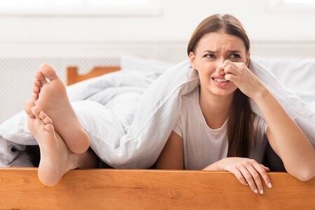 Piernas malolientes. Mujer disgustada acostada cerca de sus novios pies apestosos y pellizcar la nariz en la cama interior. Enfoque selectivo