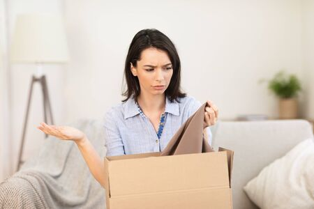 Confused girl looking at clothes in box, shipping mistake, copyspace