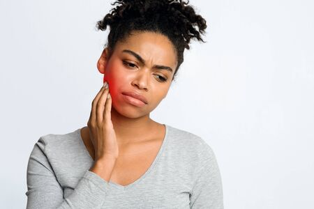 Dental problems. Afro woman suffering from inflamed gums, touching her cheek, grey background, free space