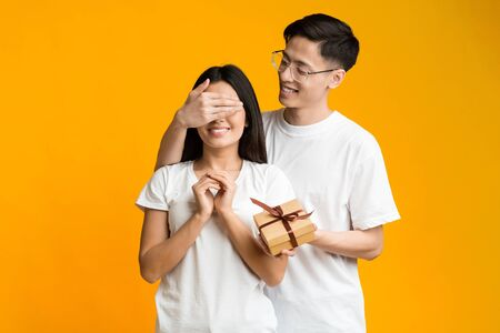 Cheerful asian guy making surprise to his excited girlfriend, covering her eyes, holding gift box