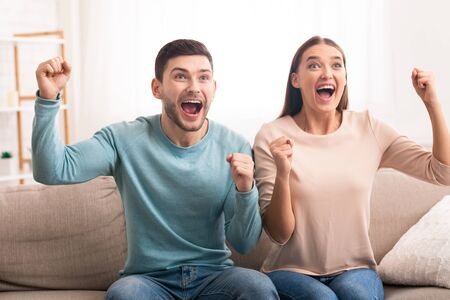 Excited Couple Watching Sports On TV Shouting And Cheering Favorite Team Sitting On Sofa At Home. Relationship And Common Interests