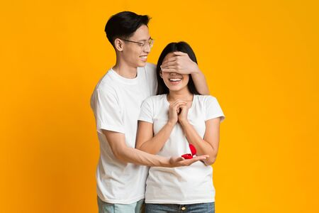 Engagement, romantic concept. Asian young man covering his girlfriend eyes, making proposal with beautiful ring, orange background