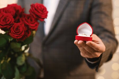 Proposal Concept. Unrecognizable man holding box with diamond ring and roses bouquet, proposing to marry, closeup
