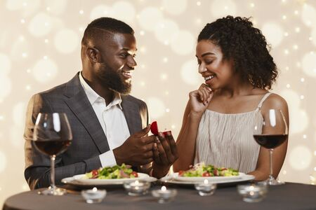 Marriage Proposal At Valentines Day. Young afro man making marriage proposal to his surprised pretty woman while having dinner at restaurant