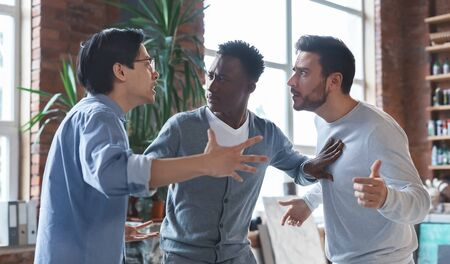 Office conflict. Angry multiracial young men fighting at workplace, afro guy standing between them