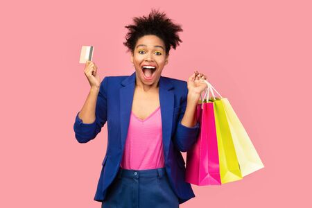 Excited black woman holding credit card and paper bags over pink studio wall, copyspace