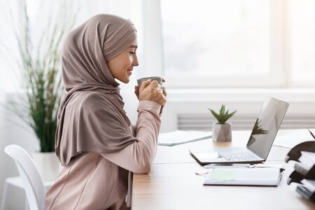 Break At Work. Young muslim female entrepreneur drinking coffee at workplace while using laptop in office, side view, free space Фото со стока