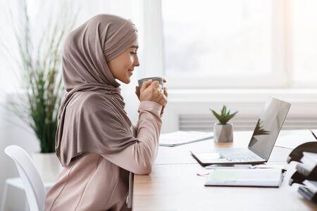 Pause bei der Arbeit. Junge muslimische Unternehmerin, die Kaffee am Arbeitsplatz trinkt, während sie Laptop im Büro verwendet, Seitenansicht, freier Raum Standard-Bild