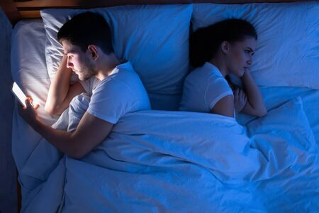 Cheating Boyfriend. Man Texting On Phone Lying Near Jealous Girlfriend In Bed At Night. Top View, Low Light